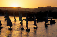 Feluccas sailing on the Nile river at sunset, Aswan, Egypt.