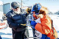 "Race Marshal Mark Nordman with last place finisher and Red Lantern Award winner Cindy Abbott gives her the ""Widow's Lamp"" to extinquish signifying the last musher on the trail has reached Nome. At the finish lin  in Nome during the 2017 Iditarod on Saturday March 18, 2017.<br /> <br /> Photo by Jeff Schultz/SchultzPhoto.com  (C) 2017  ALL RIGHTS RESERVED"