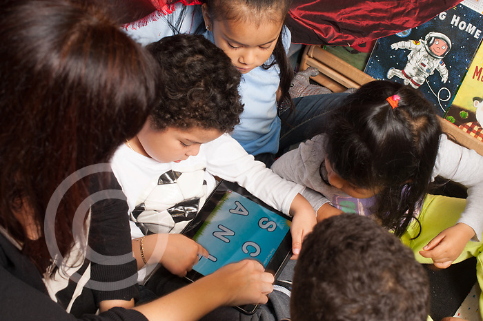 Education Preschool 3-4 year olds adult using ipad for session with boy other children clustering around to watch