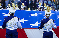 Husky Band members hold a giant American flag during the playing of the national anthem.