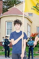 """A young person holds a Gadsden flag and as people gather for an anti-lockdown protest organized by the alt-right group Super Happy Fun America near the home of Massachusetts governor Charlie Baker in Swampscott, Massachusetts, on Sat., May 16, 2020. The protest was in defiance of Massachusetts orders mandating face coverings and social distancing and prohibiting gatherings larger than 10 people during the ongoing Coronavirus (COVID-19) global pandemic. The state's stay-at-home order is expected to be updated on May 18, 2020, with a phased reopening plan issued by the governor as COVID-19 cases continue to decrease. Anti-lockdown protests such as this have become a conservative cause and have been celebrated by US president Donald Trump. Many of the protestors displayed pro-Trump messages or wore Trump campaign hats and shirts with phrases including """"Trump 2020"""" and """"Keep America Great."""" Super Happy Fun America, organizers of the protest, are an alt-right organization best known for creating the 2019 Boston Straight Pride Parade."""
