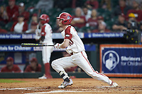 Matt Goodheart (10) of the Arkansas Razorbacks follows through on his swing against the Baylor Bears in game nine of the 2020 Shriners Hospitals for Children College Classic at Minute Maid Park on March 1, 2020 in Houston, Texas. The Bears defeated the Razorbacks 3-2. (Brian Westerholt/Four Seam Images)