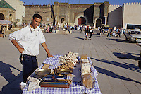 Meknes, Morocco.  Place Hedime Candy Vendor.  Bab Mansour in Background, built 1672-1732, entrance to the imperial quarter.