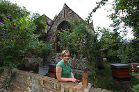 """Camilla Goddart, 38 years old, posing in front of her first hive in the garden of St Peters Church in Brocley where she started 8 years ago. Since, this graphic designer by training created a company, """"Capital Bee"""", that sells honey in the markets or in shops and cafÈs like Broca Market, Brockley, The Frog on the Green Deli in Nunhead, Cafe Crema in New Cross and El's Kitchen in Ladywell. ? ????<br /> ´ I go through various obsessions, when I was young it was growing tropical fruit, when I was at Cambridge it was English Literature, then art, then japanese woodcuts, then extraordinary victorian copper jellymoulds for puddings at banquets, then herbs and their uses, then decorative vegetable gardens and making potagers, then antique african masks, though in the end keeping bees has proved to be the most enduring as they are so complex and are teaching me all the time about their mysterious world.  I even look after nests of bumblebees now in wooden boxes in the apiary they are terrific characters, people get them mixed up with bees and sometimes want them removed, though it is always best to leave them alone ideally as they rarely do any harm!???? ª"""