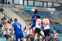 Miles Welch-Hayes of Cpolchestder United gets his head to the ball under pressure from Jombati and Hamer during Colchester United vs Oldham Athletic, Sky Bet EFL League 2 Football at the JobServe Community Stadium on 3rd October 2020