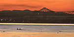 A couple paddle across the San Francisco Bay viewing be a bridge in the foreground.