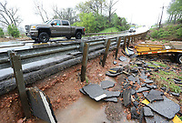 Traffic passes over layers of asphalt peeled from the roadway on a low water bridge Wednesday, April 28, 2021, on W. Monroe Avenue in Lowell because of flash flooding. The National Weather Service office in Tulsa said the storm system that began moving through Northwest Arkansas Tuesday night had dropped from 1 to 3 inches of rain across the area by mid-morning Wednesday. With rainfall of 4 to 6 inches being reported in some areas. Check out nwaonline.com/210429Daily/ and nwadg.com/photos for a photo gallery.<br /> (NWA Democrat-Gazette/David Gottschalk)