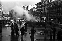 Carrefour boulevard Lazare-Carnot et allées François-Verdier, devant le Monuments aux Combattants. 6 février 1978. Scène de manifestation : au 1er plan groupe de manifestants de dos et de profil ; au 2nd plan pompiers en train d'éteindre un camion en feu, fumée, fourgon de police, bus ; en arrière-plan perspective du boulevard Lazare-Carnot, plan d'ensemble façades. Cliché pris lors d'une manifestation organisée par une trentaine de transporteurs et artisans locaux pour protester contre le chantier de l'autoroute A61 donné à une grosse société du centre de la France. Manifestation patronée par la Confédération Intersyndicale de Défense et d'Union Nationale des Travailleurs Indépendants (CIDUNATI).