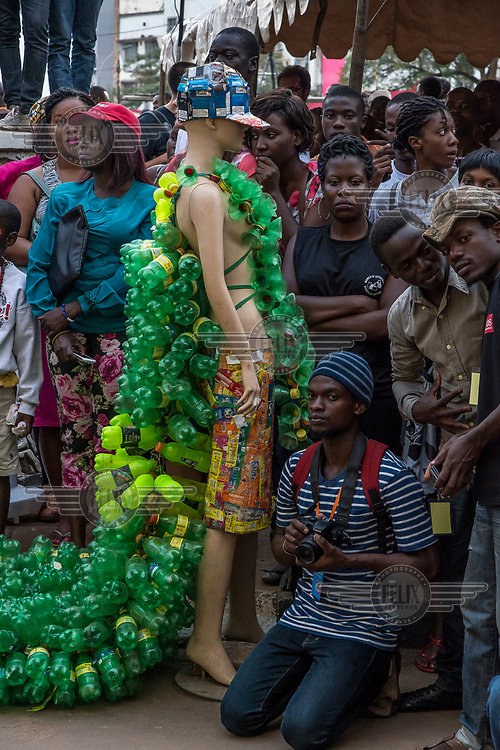 In the middle of the audience, during the Bayimba cultural festival at the Kampala National Theatre, the artist Gisa Jr Gong Brian, who creates, with members of his group Afrika Arts Kollective, pieces from plastic waste. A mannequin is wearing a dress they made with a train of plastic bottles and a hat made from empty packets of cigarettes.