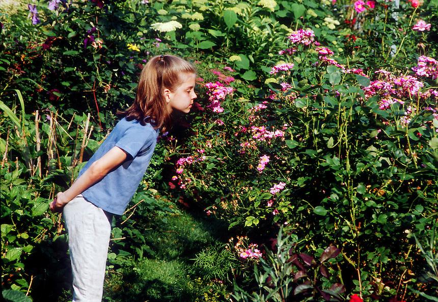 Girl smelling flowers in garden.