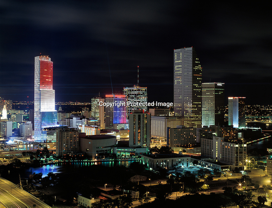 City view of Miami at night decorated with red, white and blue patriotic colors. Laser show and the word USA can be seen in the buildings.