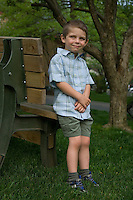 Smiling young boy in green shirt and shorts stands next to wooden bench in yard
