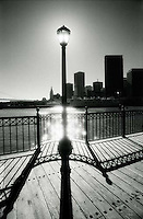 Back lit street lamp on pier with silhouetted buildings in the background<br />