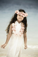 Young girl with plumeria head and neck lei at beach, Hawaii