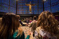 """Friedenslicht von Bethlehem kommt als Zeichen gegen Terror und Gewalt nach Berlin.<br /> Die Kaiser-Wilhelm-Gedaechtnis-Kirchengemeinde empfing am dritten Adventssonntag das Friedenslicht von Bethlehem. Mehr als 500 Pfadfinderinnen und Pfadfinder brachten das Licht in die Kirche, wo es mit einem oekumenischen Gottesdienst empfangen wurde. Die Gedaechtniskirche wurde von den Pfadfinderverbaenden als Ort fuer die Uebergabe des Lichtes ausgewaehlt, um kurz vor dem Jahrestag des Anschlags auf dem Breitscheidplatz ein Zeichen gegen Terror und Gewalt zu setzen. <br /> Das Licht wird bei den Gedenkandachten und -veranstaltungen am 19. Dezember 2017, dem Jahrestag des Anschlags, als Quelle aller Kerzenflammen, z.B. auch bei der Lichterkette am Abend dienen.<br /> Das Friedenslicht ist eine Initiative des Oesterreichischen Rundfunks (ORF). Es wird seit 1986 in der Geburtsgrotte Jesu in Bethlehem von einem Kind entzuendet und nach Wien gebracht. Als Symbol fuer den Wunsch nach Frieden und der Sehnsucht nach einer gerechten und solidarischen Welt tragen Pfadfinderinnen und Pfadfinder das Licht am dritten Advent in ihre Heimatlaender. In Deutschland steht die diesjaehrige Friedenslichtaktion unter dem Motto: """"Auf dem Weg zum Frieden"""".<br /> In der Kaiser-Wilhelm-Gedaechtnis-Kirche wird das Friedenslicht bis zum Ende der Weihnachtszeit in einer Leuchte an einem zentralen Ort brennen. An der Flamme kann jeder eine Kerze entzuenden und das Licht auf diese Weise an andere Menschen weitergeben – beispielsweise in Kirchengemeinden oder Schulen.<br /> Im Bild: Bruder Pascal Sommerstorfer spricht mit den Gottesdienstteilnehmern das Vater Unser.<br /> 17.12.2017, Berlin<br /> Copyright: Christian-Ditsch.de<br /> [Inhaltsveraendernde Manipulation des Fotos nur nach ausdruecklicher Genehmigung des Fotografen. Vereinbarungen ueber Abtretung von Persoenlichkeitsrechten/Model Release der abgebildeten Person/Personen liegen nicht vor. NO MODEL RELEASE! Nur fuer Redaktionelle Zwecke. Don't pub"""