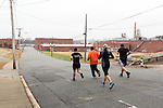 December 22, 2014. Lexington, North Carolina.<br />  Mayor Newell Clark, left, leads his workout group on a run near the abandoned Lexington Furniture factory as part of their workout routine.<br />   Newell Clark, the 43 year old mayor of Lexington, NC, leads a group of friends and colleagues on a 4 times a week exercise routine around downtown. The group uses existing infrastructure, such as an abandoned furniture factory, loading docks, stairs, and handrails to get fit and increase awareness of healthy lifestyles in a town more known for BBQ.<br /> Jeremy M. Lange for the Wall Street Journal<br /> Workout_Clark