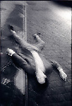 Man'sbody laying on cobblestone street