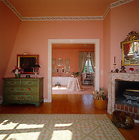 A bathroom is situated at one end of this bedroom and shares the pretty green and pink colour scheme