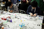"""Visitors enjoy constructing scale model toys during the Niconico Douga fan event at Makuhari Messe International Exhibition Hall on April 25, 2015, Chiba, Japan. The event includes special attractions such as J-pop concerts, Sumo and Pro Wrestling matches, cosplay and manga and various robot performances and is broadcast live on via the video-sharing site. Niconico Douga (in English """"Smiley, Smiley Video"""") is one of Japan's biggest video community sites where users can upload, view, share videos and write comments directly in real time, creating a sense of a shared watching. According to the organizers more than 200,000 viewers for two days will see the event by internet. The popular event is held in all 11 halls of the huge Makuhari Messe exhibition center from April 25 to 26. (Photo by Rodrigo Reyes Marin/AFLO)"""
