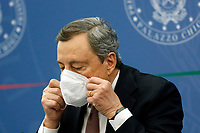 The Italian premier Mario Draghi tens on a face mask during the press conference after the minister's cabinet.<br /> Rome (Italy), October 5th 2021<br /> Photo Samantha Zucchi Insidefoto