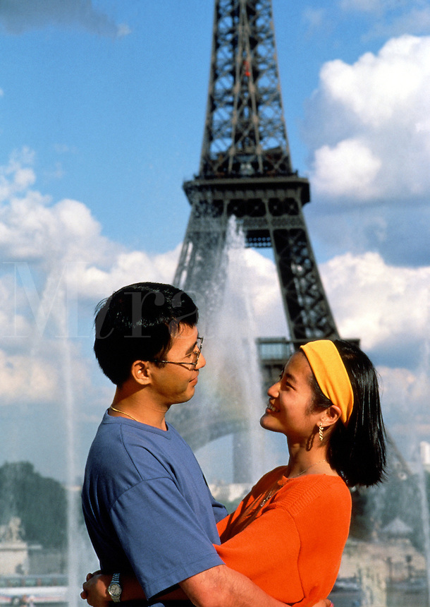 A smiling, romantic Asian couple poses in an embrace in front of the Eiffel Tower. Paris, France.