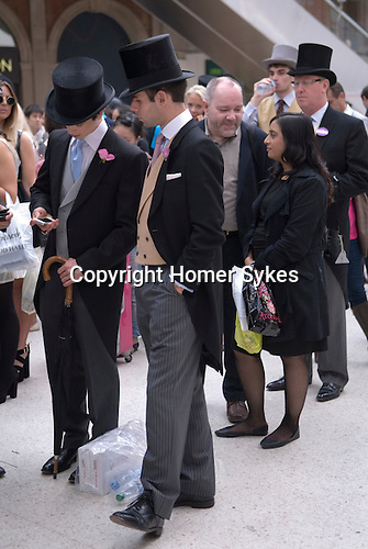 Waterloo Train Station London. Men in top hat and tail coats buying train tickets for Ascot. Royal Ascot horse racing Berkshire. 2012