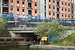 © Joel Goodman - 07973 332324 . 30/04/2017 . Salford, UK . Valeriy (43) , from Lithuania , with development above . Homeless men are living in a towpath tunnel in Saford , in the shadow of the Ordsall Chord railway link and a large , Chinese-backed housing development. Photo credit : Joel Goodman
