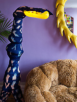 In the living room, the woven platypus-looking standing lamp and the yellow resin mirror is by Misha Kahn; the Campana Brothers designed the furry couch.