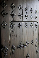 A detail of a heavy wooden door studded with iron work