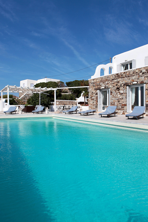 luxury pool area with deck chairs
