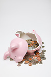 Broken piggy bank with coins spilling out