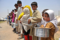 Children wait in line for food at the Swabi refugee camp. Three times a day hot meals are distributed in the camp. At present there's a lack of cooking facilities where the people can cook themselves. The camp is run by Red Cross/Red Crescent (ICRC) and and is home to about 18,000 refugees. The Pakistani government began an offensive against the Taliban in the Swat Valley in April 2009, which led to a major humanitarian crisis. Up to two million civilians were estimated to have been displaced by the fighting.