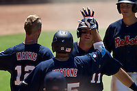 Outfielder Zach Kirksey #11 of the Ole Miss Rebels is greeted in the dougout after scoring during the NCAA Regional baseball game against the Texas Christian University Horned Frogs on June 1, 2012 at Blue Bell Park in College Station, Texas. Ole Miss defeated TCU 6-2. (Andrew Woolley/Four Seam Images).
