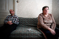 Sasha and Lyuba Boichuk watch a stand-up comedy show during the New Years holiday. Lyuba blames the Chernobyl accident for their son's murder, but Sasha blames himself. At the time of the accident, the Boichuks were just starting to build themselves this house in Sukachi, Ukraine. After some hesitation, they kept building and have lived here ever since. <br /> ------------------- <br /> This photograph is part of Michael Forster Rothbart's After Chernobyl documentary photography project.<br /> © Michael Forster Rothbart 2007-2010.<br /> www.afterchernobyl.com<br /> www.mfrphoto.com <br /> 607-267-4893 o 607-432-5984<br /> 5 Draper St, Oneonta, NY 13820<br /> 86 Three Mile Pond Rd, Vassalboro, ME 04989<br /> info@mfrphoto.com<br /> Photo by: Michael Forster Rothbart<br /> Date:  1/2009    File#:  Canon 5D digital camera frame 6210 <br /> ------------------- <br /> Original caption: .Photo title:.New Year's holiday in Sukachi. ..Short caption: .Lyuba Boichuk blames the Chernobyl accident for their son's murder, but her husband Sasha blames himself...Full caption: .Sasha and Lyuba Boichuk watch a stand-up comedy show on TV during the New Years holiday. At the time of the 1986 accident, Sasha and Lyuba were just starting to build themselves this house in Sukachi. After some hesitation, they decided to continue building and have lived here ever since.  .     Sasha worked as a liquidator in the Chernobyl clean-up efforts. Afterwards, he began to drink heavily, and says he lost a decade of his life to alcohol. He blames himself for the death of his son, who disappeared outside a local bar and is believed to have been murdered during a robbery. .-------------------.