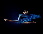 Artistic surreal photo of a beautiful woman in a dynamic front split in mid-air with flowing blue cloth wrapping her nude body on black background Image © MaximImages, License at https://www.maximimages.com