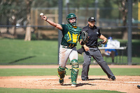 Oakland Athletics catcher Matt Cross (77) throws to first base during an Instructional League game against the Los Angeles Dodgers at Camelback Ranch on October 4, 2018 in Glendale, Arizona. (Zachary Lucy/Four Seam Images)