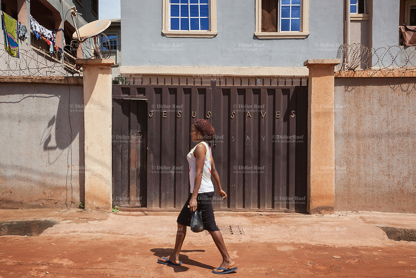 """Nigeria. Enugu State. Enugu. Town center. An Igbo woman walks on a dirt road and passes in front of a  private house's gate where the following words are written """" Jesus Saves Saves"""". The second Saves is handwritten with chalk. Satellite dish and barbed wires. Enugu is the capital of Enugu State, located in southeastern Nigeria. Flip-flops are a type of sandal, typically worn as a form of casual wear. They consist of a flat sole held loosely on the foot by a Y-shaped strap known as a toe thong that passes between the first and second toes and around both sides of the foot or can be a hard base with a strap across all the toes (these can also be called sliders). Enugu is the capital of Enugu State, located in southeastern Nigeria. 2.07.19 © 2019 Didier Ruef"""