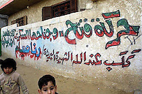 """At the entrance of a house in which seven years old girl Rama Syian was killed by Israeli fire a graffiti announce: """"The Fatah movement and it's military wing mourns with God the """"Martyr"""", the innocent Rama Syian"""", the girl was having lunch with the family when a bullet hit her head, killing her immediately. Amar Abed was among the artists who wrote the graffiti at the entrance of the house and all around the block, in Khan Yunis, Gaza. Photo by Quique Kierszenbaum"""