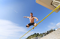 BNPS.co.uk (01202 558833)<br /> Pic: BNPS<br /> <br /> Pictured: Slackliner, Colin Pullock leaps towards the blue skies at Boscombe<br /> <br /> Weather input - Warm weather in Bournemouth<br /> <br /> People made the most of the late September sun at Bournemouth beach in Dorset today (Sunday).