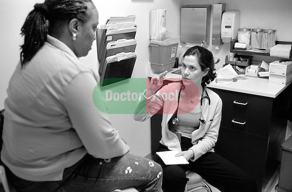 Young female internal medicine resident physician seated speaking and gesturing to middle age African-American female sitting on examination table