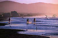 People play along the beach during soft summer light in La Serena on its way to becoming Chile's premier beach resort. La Serena enjoys a transitional climate between the arid northern desert of the Atacama and the pleasant Mediterranean climate of the central coast.
