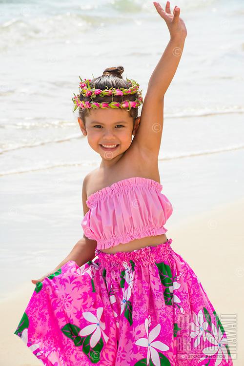 A young local girl waves as she holds her pink pa'u (skirt) on Lanikai Beach in Kailua, Windward O'ahu.