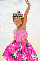 A young local girl waves as she holds her pink pa'u (skirt) on Lanikai Beach in Kailua, Windward O'ahu.