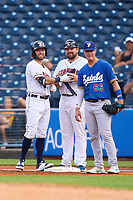 Toledo Mud Hens Kody Clemens (23) with coach CJ Wamsley after hitting an infield single during a game against the St. Paul Saints on August 26, 2021 at Fifth Third Field in Toledo, Ohio.  First baseman Jose Miranda (66) looks on.  (Mike Janes/Four Seam Images)