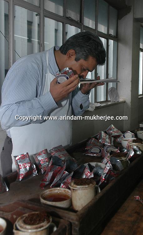A tea tester smells tea in the tea testing room of J. Thomas ltd. company in Kolkata, West Bengal,  India,  Arindam Mukherjee