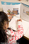 Education preschoool children ages 3-5 art activity girl drawing with picture book propped up in front of her copying the drawing vertical