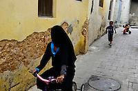 TANZANIA Zanzibar, Stone town is part of UNESCO heritage, muslim girl enjoys bicycle ride / TANSANIA Insel Sansibar, Stonetown, die Altstadt ist Teil des Unesco Welterbe Programm, 99 Prozent der Bewohner sind Muslime