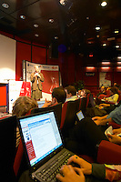 Ben Hammersley, writer author and consultant, the auditorium amphi amphitheatre with conference participants delegates audience all with laptop computers connected with wireless internet chatting and commenting on the debate online, screens in the foreground at the Les Blog conference in Paris December 2005 on blogging, new media and internet strategy