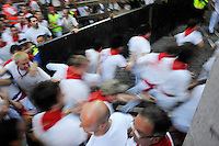 The carpenters close the fence after six Valdefresno fighting bulls have passed Mercaderes curve during the third running of the bulls of San Fermin, on July 9, 2013, in Pamplona, Basque Country. On each day of the eight San Fermin festival days six bulls are released at 8:00 a.m. (0600 GMT) to run from their corral through the narrow, cobbled streets of the old navarre town over an 850-meter (yard) course. Ahead of them are the runners, who try to stay close to the bulls without falling over or being gored. (Ander Gillenea / Bostok Photo)