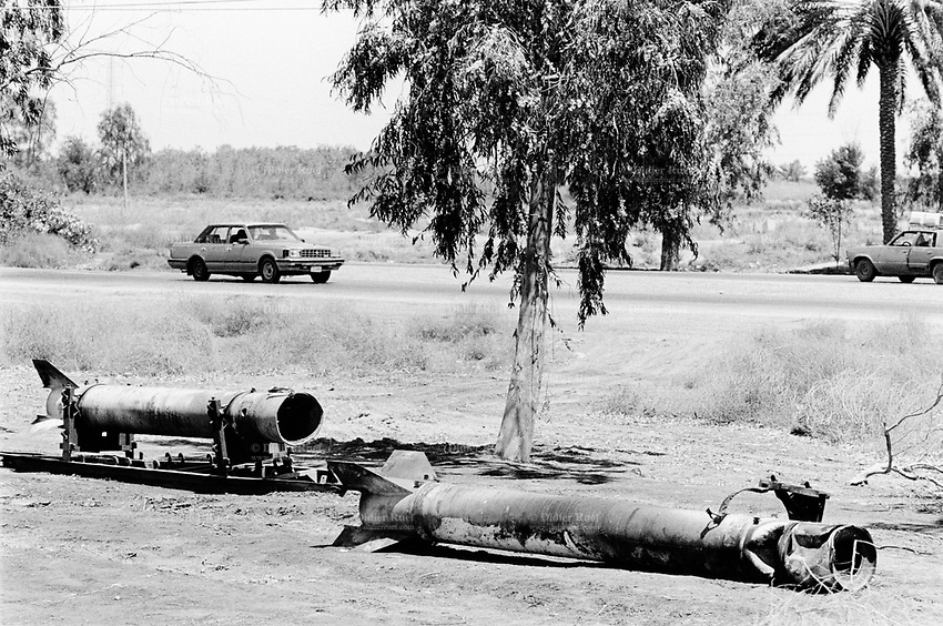 Iraq. Baghdad. Traffic on Mossul road and waste of the war. The coalition forces (american army) have left two destroyed Al Samud missiles. The derelict weapons lay on the ground. © 2003 Didier Ruef
